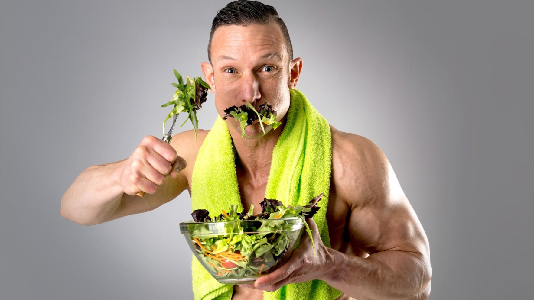 Der sportliche Mann stopft sich Salat in den Mund. | Spiele.de