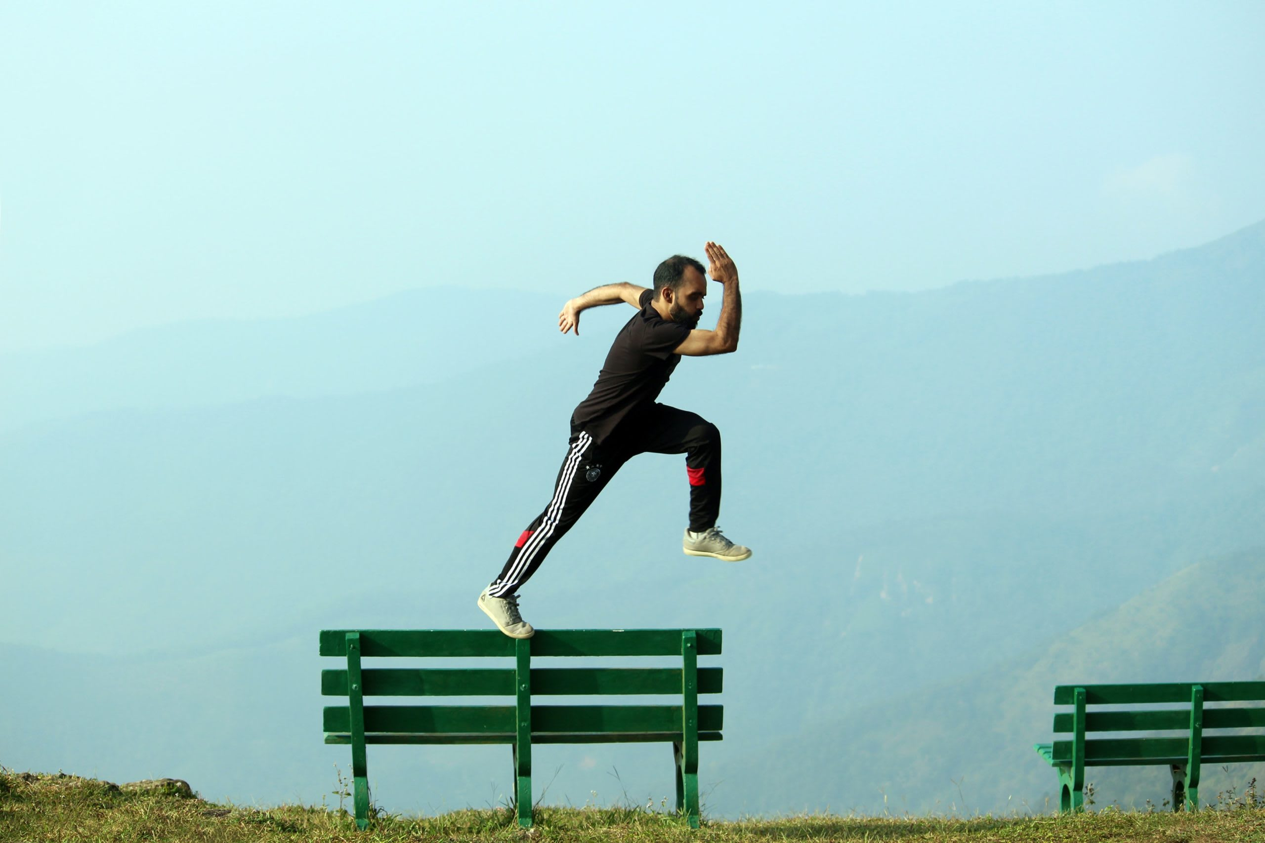 Man jumping from one bench to another