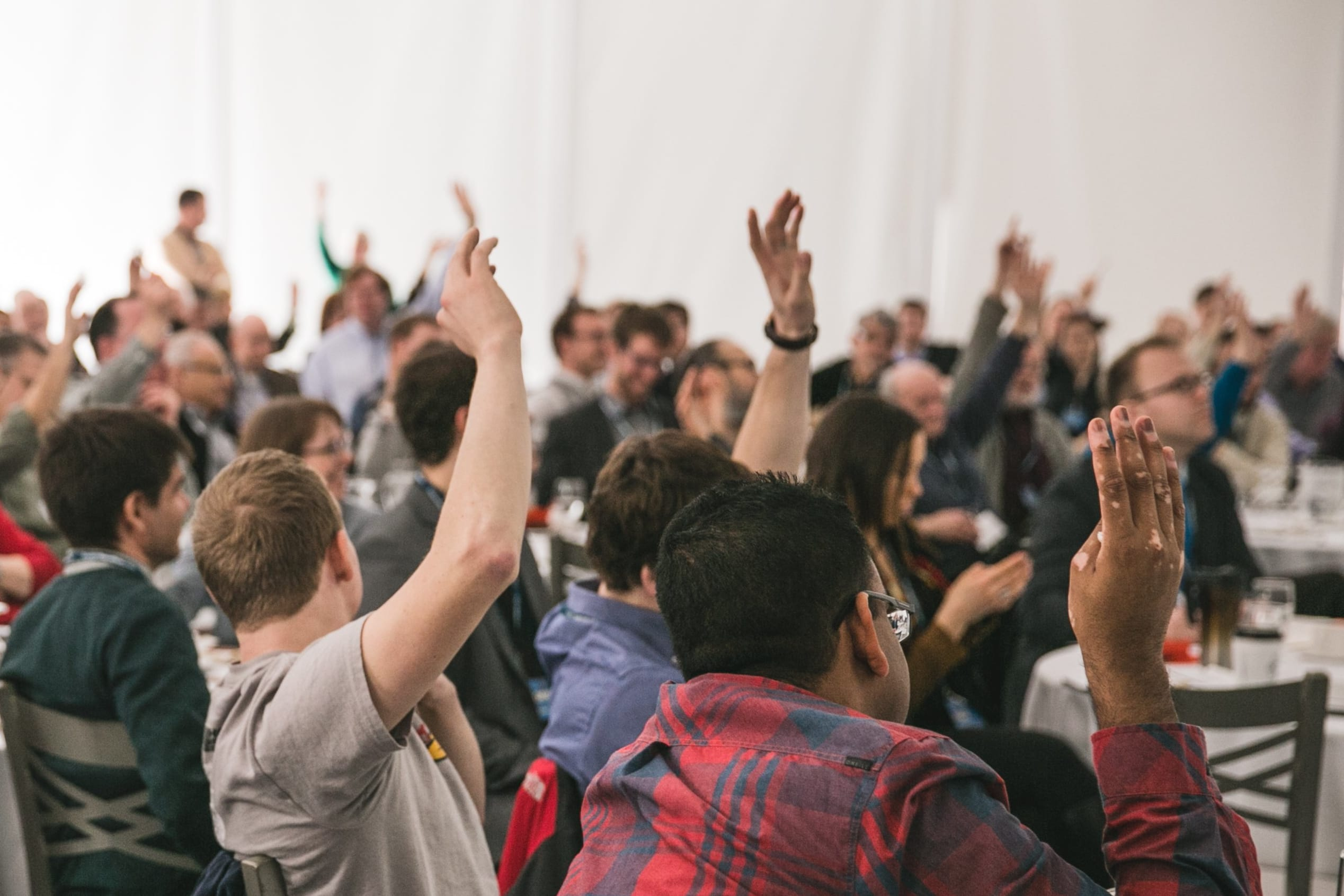 Students have hands raised in class