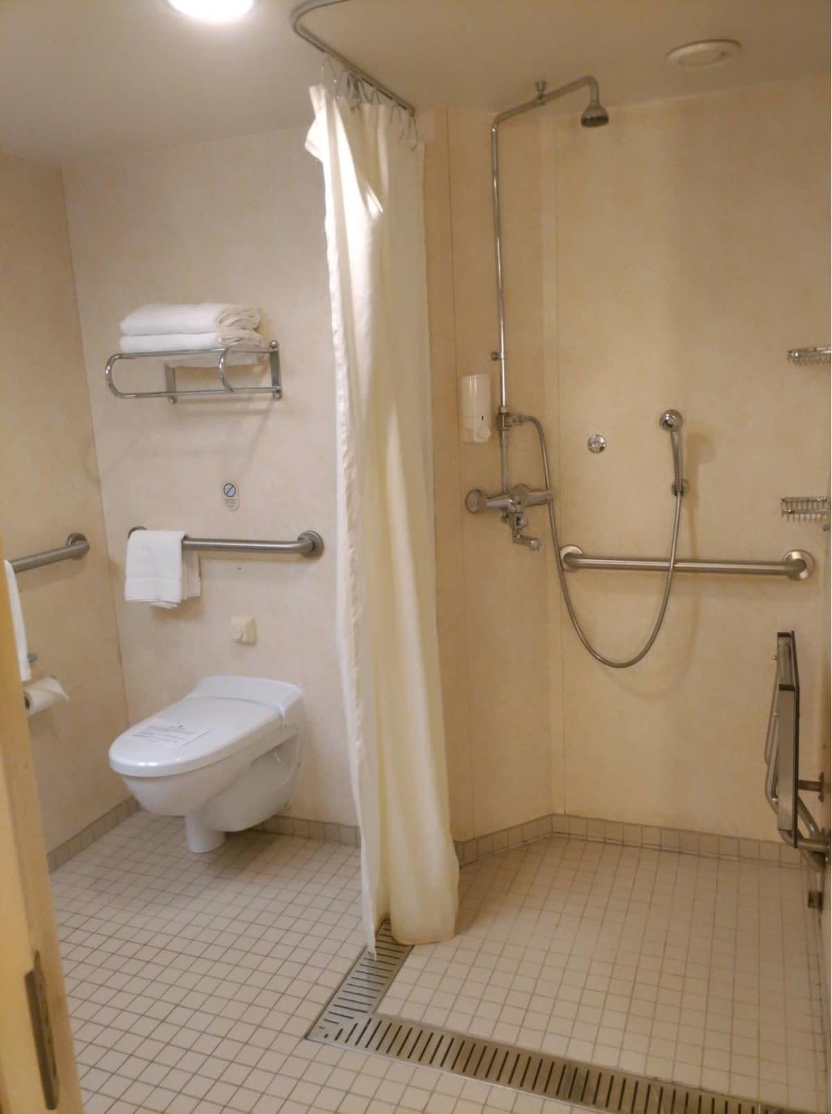 車椅子のまま入れる広さのトイレやシャワー。シャワーの右の壁に椅子が折りたたまれてます。広げると座ってシャワーが利用できます。