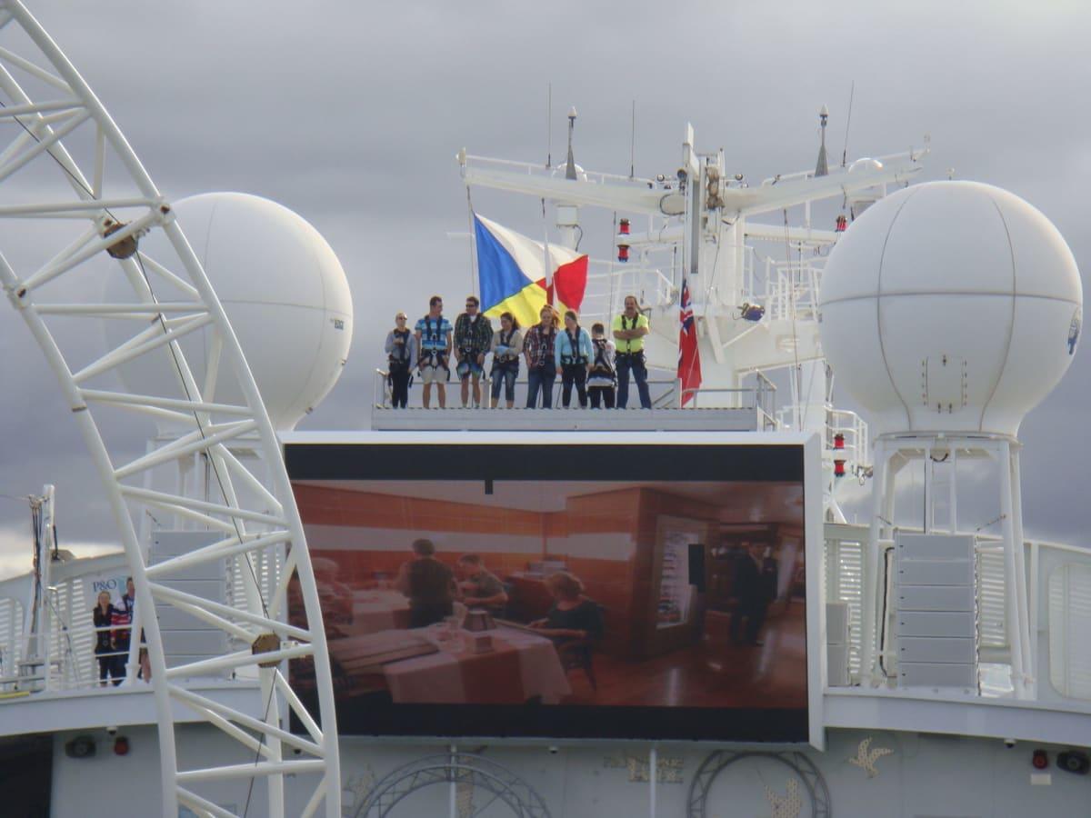 19日ブリスベン。 高い所(トップデッキのスクリーンの上)に登らせてもらい、出港の様子を眺める客。 乗船当日の(多分有料)イベントなんだが、どうやって申し込むのかな。 | 客船パシフィック・ジュエルの船内施設