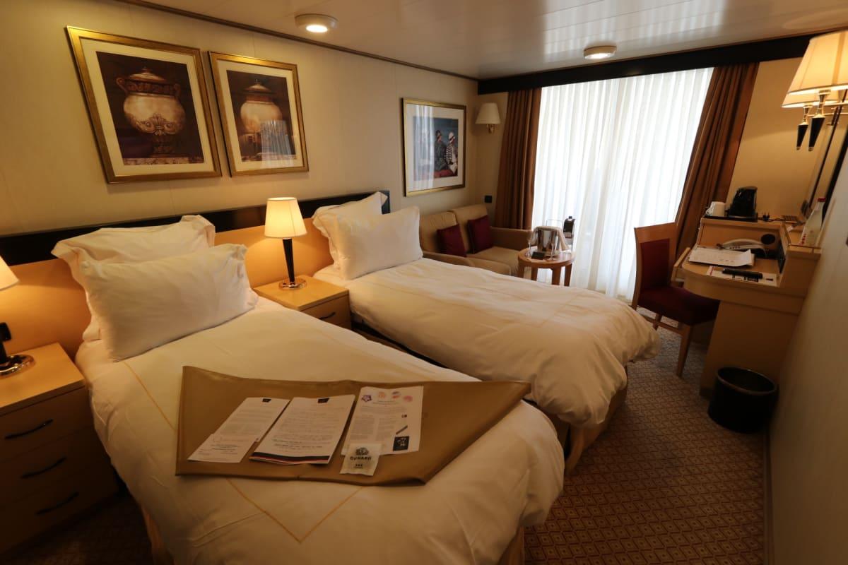 部屋に入ると、ベットの上にデイリー・プログラム、船内地図、ディナー・テーブル番号など   客船クイーン・エリザベスの客室