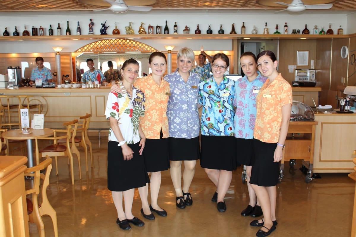ウクライナ出身のウエイトレスの皆さんが素敵な笑顔でお出迎え プロムナード・オープンバーにて | 客船ぱしふぃっくびいなすのダイニング、クルー
