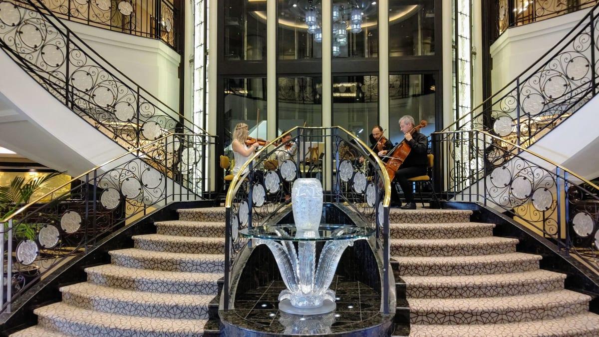 ラリック社のデザインした階段のアトリウムでの弦楽四重奏に迎えられ乗船