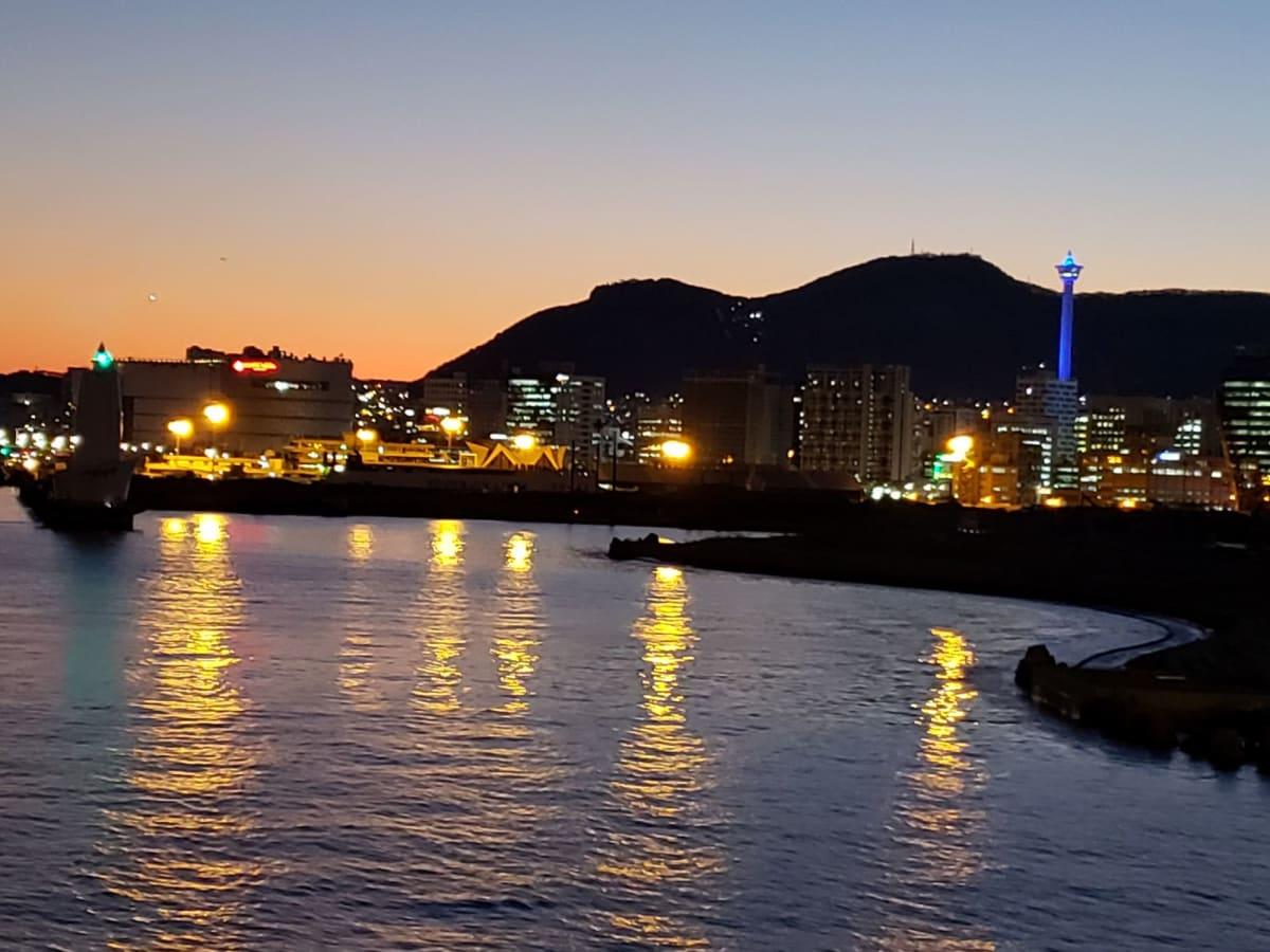 出航時の夕暮れの釜山。 左側のロッテ百貨店ロッテマート光復店の屋上は無料で、右側でライトアップされている釜山タワーに負けない眺めが楽しめます。 | 釜山