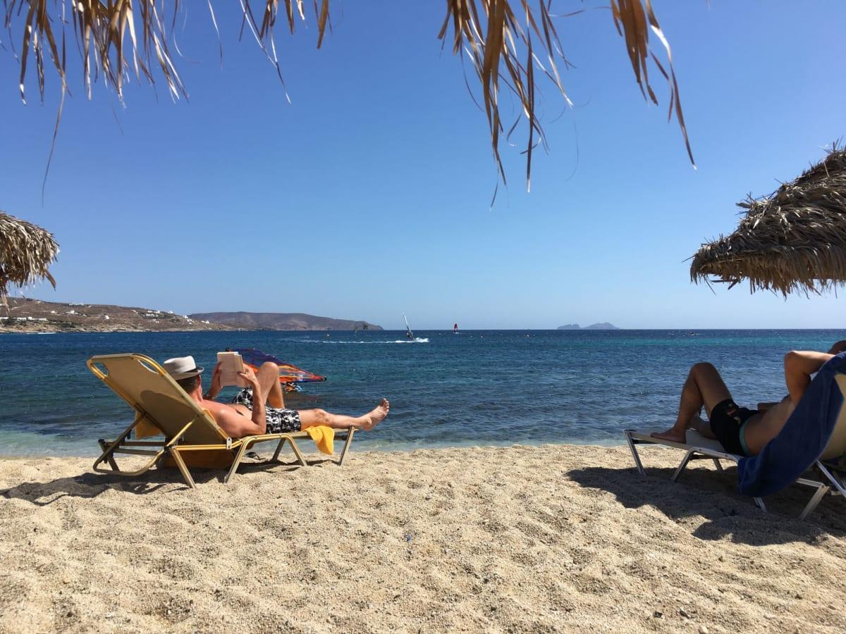 カラファティスビーチ。パラソルとベッドが無料なのでお得です。目の前のバケーションを楽しむ紳士が素敵。 | ミコノス島