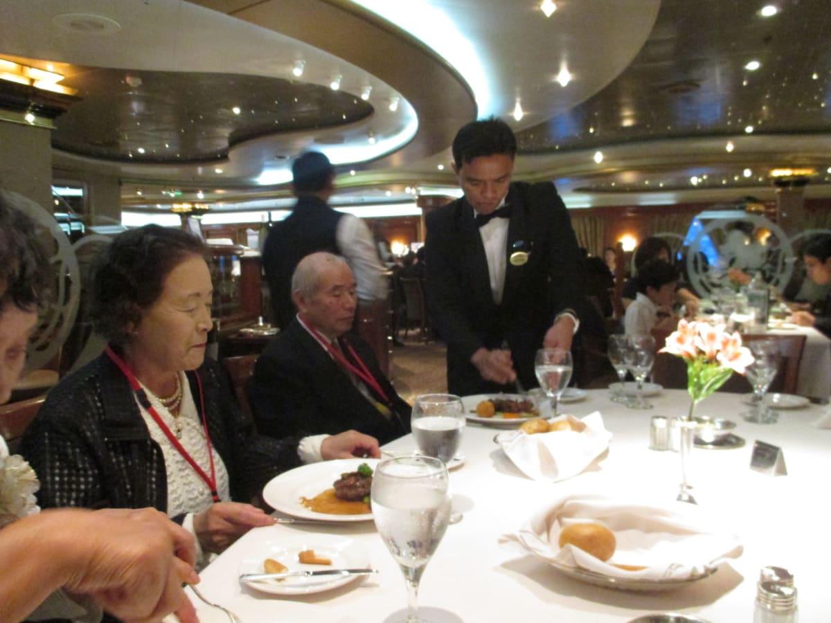 ナイフ&フォークに慣れていない義父をテーブル係が助けてくれました。ありがたい。 | 客船サン・プリンセスのダイニング、乗客、クルー