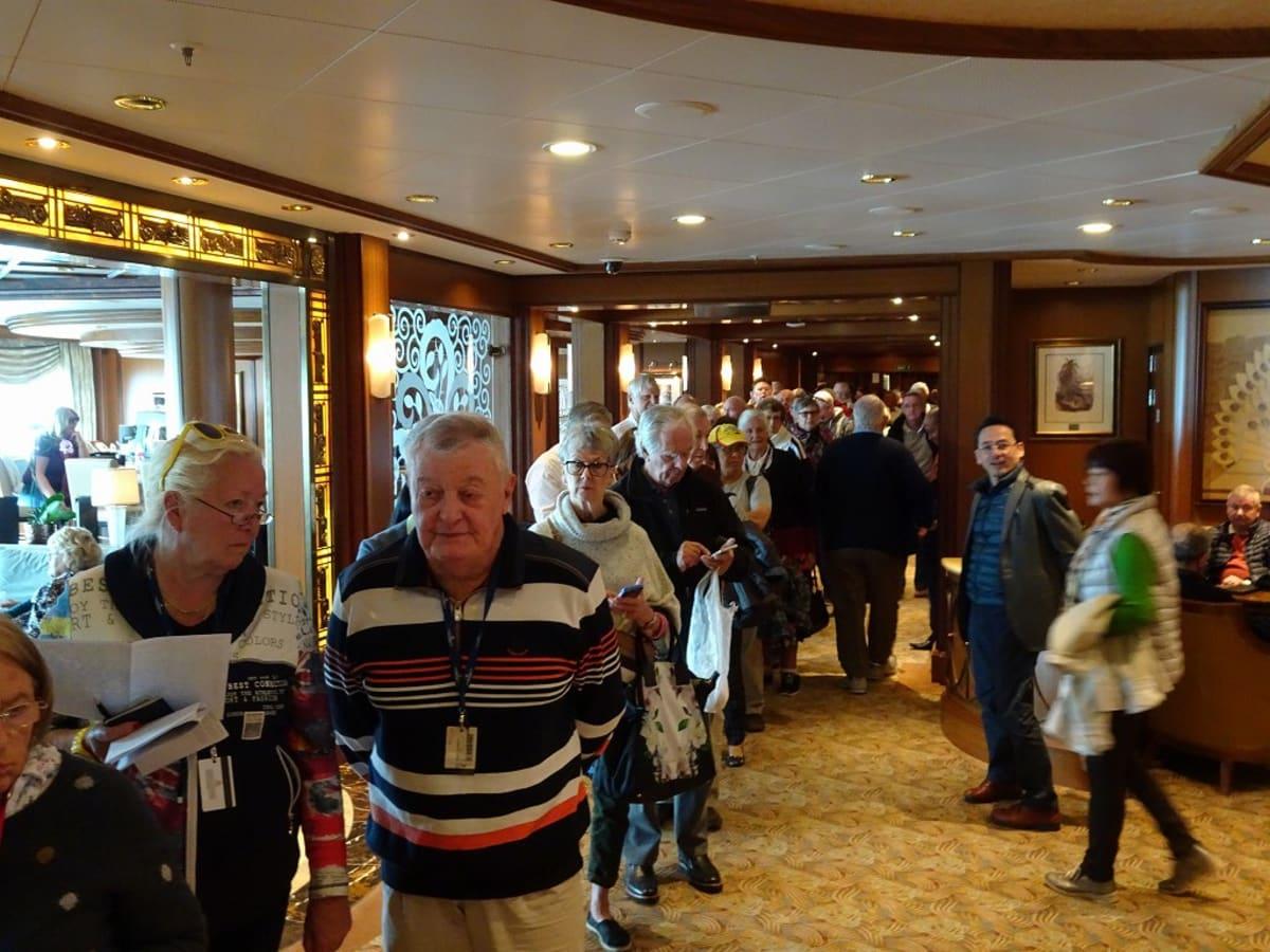 上陸許可証を受け取る為に、長蛇の列が! 外国人客ばかりが並び、日本人客は冷やかしに見に来る程度。 団体扱いの比率が高い日本人客は、ブリタニアに集まり、別扱い、観光バスでお先に市街地に出て行きました。 | 釜山での客船クイーン・エリザベス