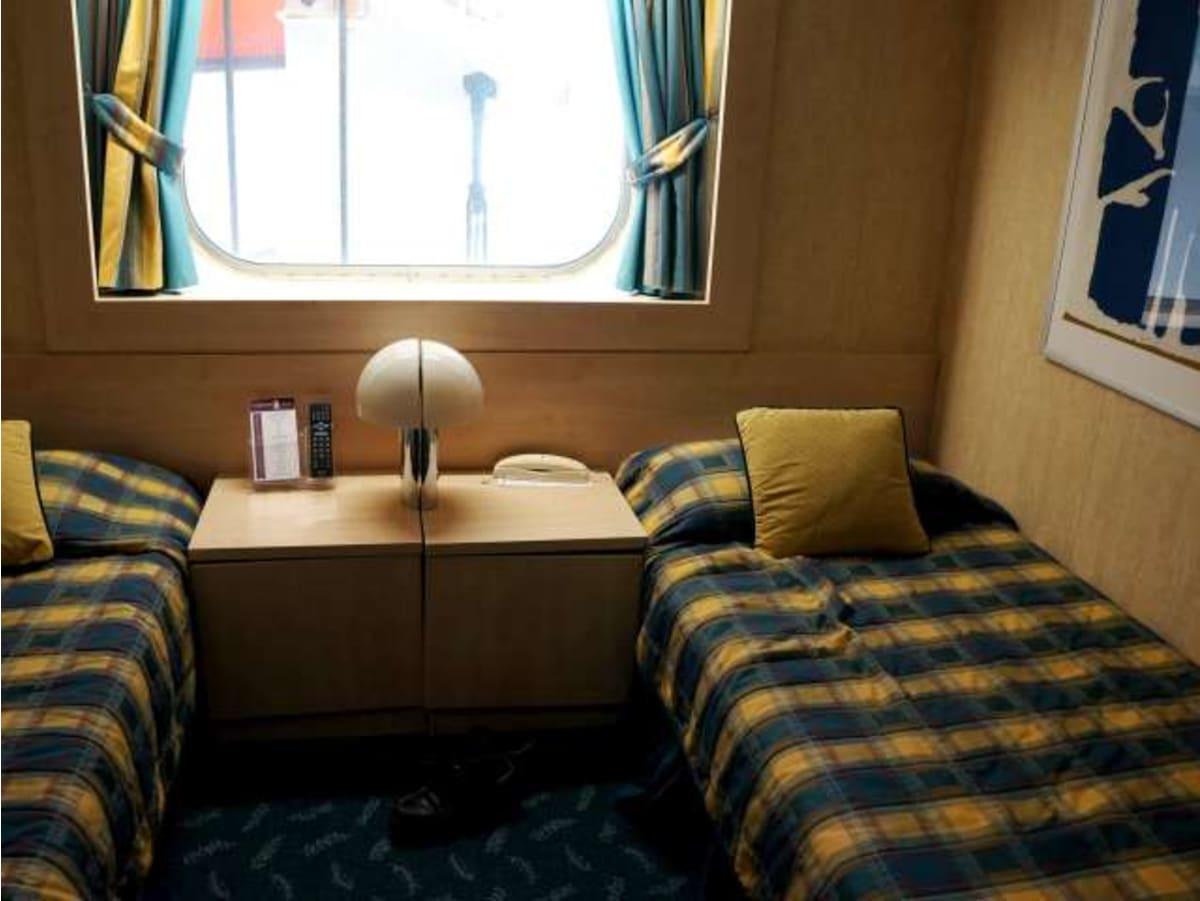 初めてのクルーズ船は、テンダーボートが窓の外にぶら下がる安価な訳あり部屋を選びました。   客船MSCアルモニアの客室