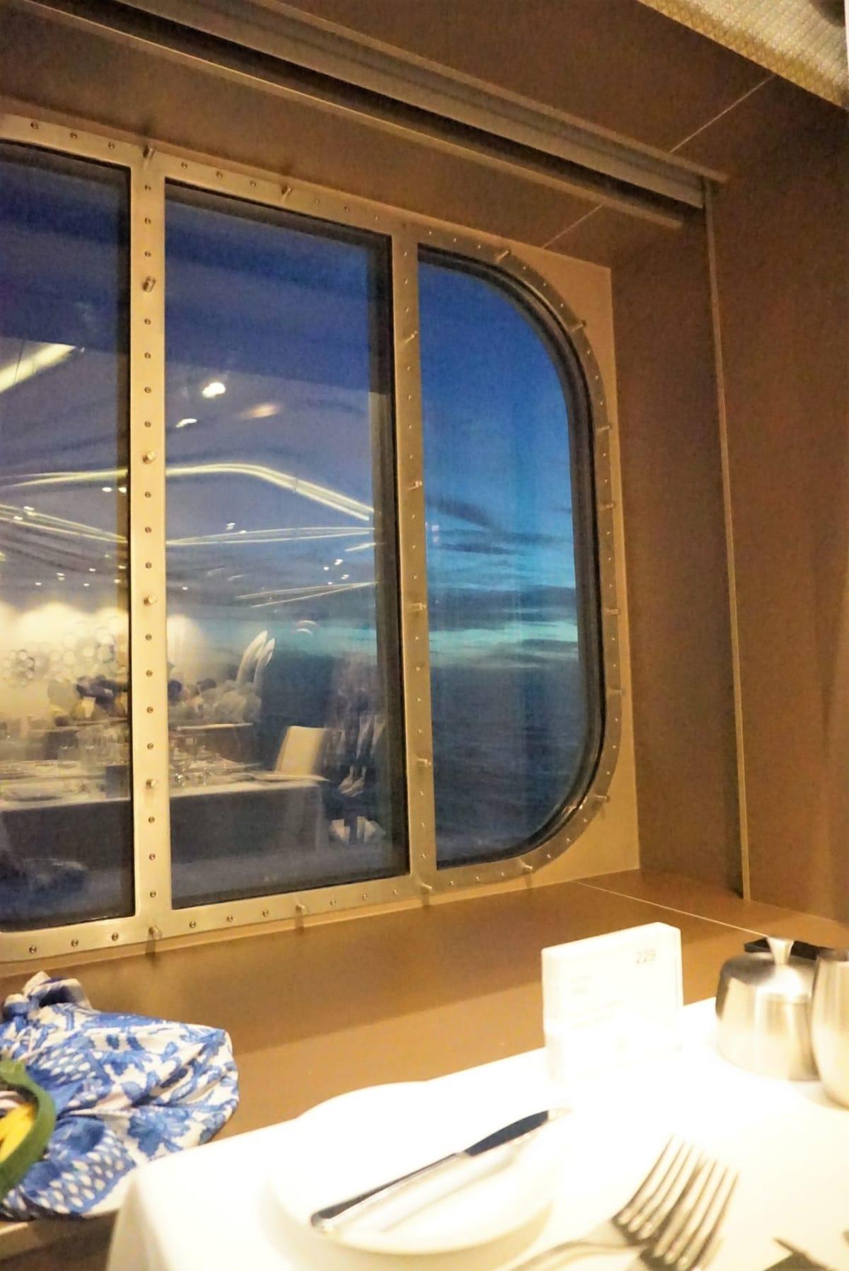 窓側2人席、夕焼けを見ながら食事がスタート | 客船アンセム・オブ・ザ・シーズのダイニング