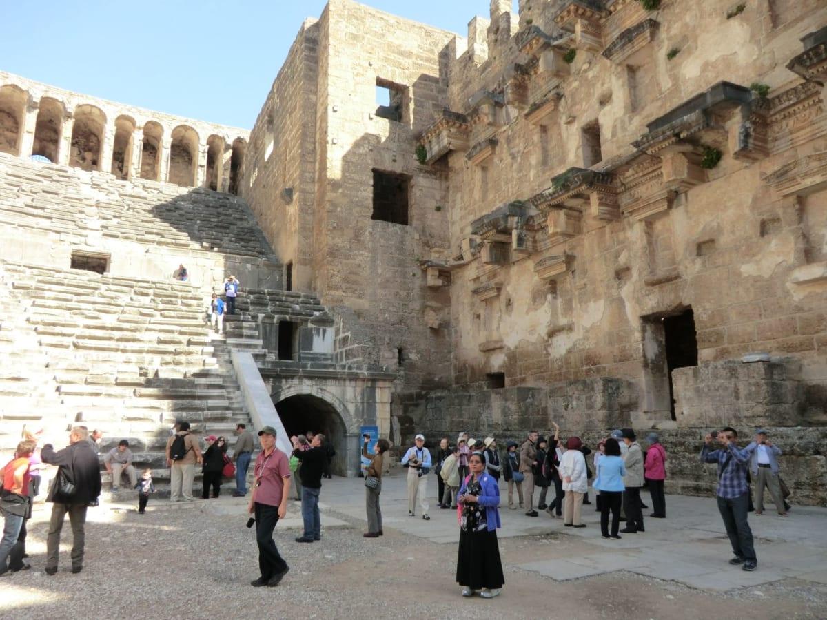 アスペンドス遺跡 ASPENDOS アランヤから 世界各地にローマ古代劇場はあるが、こちらはほぼ完壁に近い形で残っていて、トルコに残るローマ式古代劇場の代表といわれる。美しい礫岩のブロックを積んでおり、ドアや窓枠にはクリーム色の石灰岩を使っている。舞台建物には5つの入り口があり、壁にはさまざまな装飾がほどこされている。この劇場はマルクス・アウレリュース(161-180)に捧げられたものといわれる。  収容人員2万人といわれ、今でも「アスペンドス国際オペラフエテイバル」が6月から7月に開かれている。多くの観光客が訪れていた。この劇場は近くにローマ時代の水道橋があるとのことだが周りは美しいアンタルヤの平原で建物はあまりない。 | アランヤ