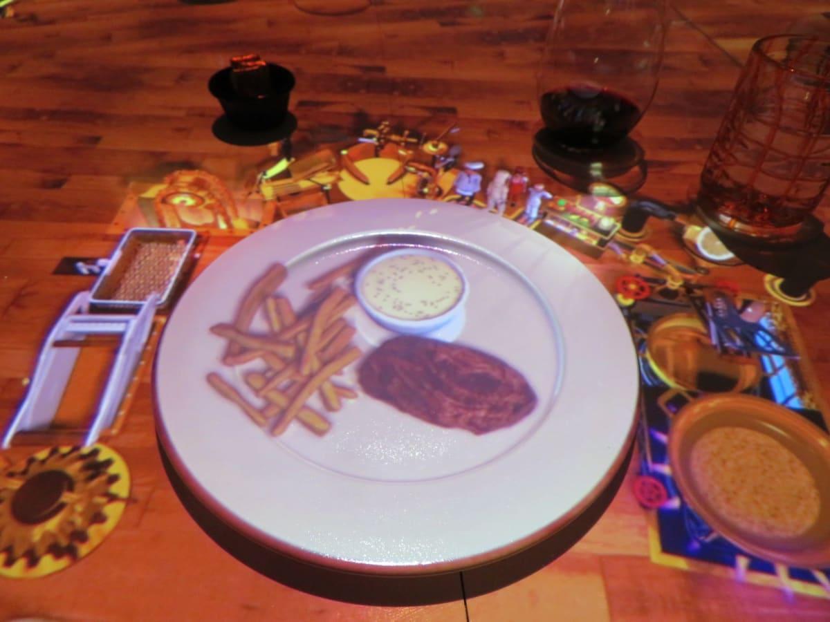 メイン料理のビーフステーキが出来上がると料理イメージが映像で映し出される。 | 客船セレブリティ・ミレニアムのダイニング