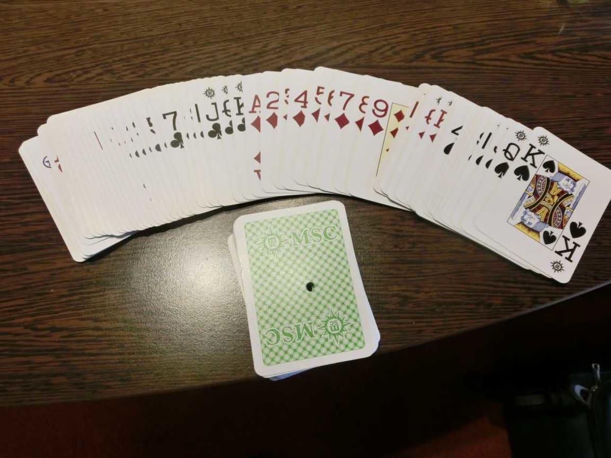 カジノのキャッシャーで1ドルで売っている使用済みのプレイングカード(トランプ)。カジノで悪用できないように、中心に穴が開けられてますが、普通に遊ぶには問題ないです。色は赤・青・黄・緑の4色あるので、好きな色を指定できます。ケース等はなく、このまま輪ゴムでとめて渡されます。(普通のカジノはケースくれるのですが...) | 客船MSCスプレンディダのアクティビティ、船内施設