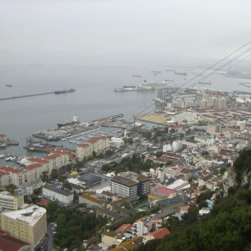 ジブラルタルGibraltar ジブラルタルはイベリア半島の南東端に南北に伸びた半島で、地中海に面し、北側はスペインと陸続き。語源はアラビア語のジブエル・アル・ターリクで、「ターリクの岩」を意味する。イギリス海軍の拠点。アフリカから連れてこられたバーバリーマカクが岩山に棲息している。このサルがジブラルタルからいなくなったら英国がジブラルタルから撤退するとの伝説があるという。  雨と風がひどい中、ケーブルでターリクノ丘山頂へ。ヨーロッパポイント、サルの山などをを観光。午後は晴れ。免税地域というだけありいろいろな店がある。但し日曜日、インド人の店以外はお休み。出港して大西洋に出ると船が揺れ出した。 | ジブラルタル