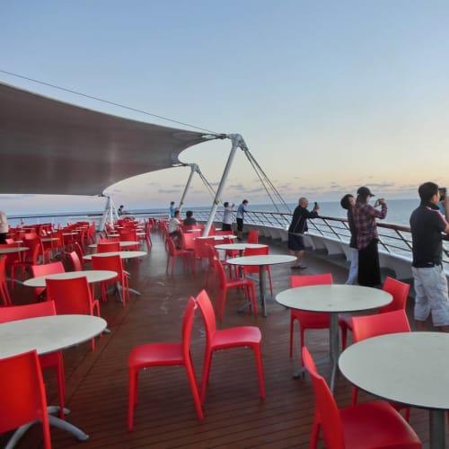 早朝、デッキ11船尾から、日の出を眺める人々。 | 客船コスタ・ビクトリアの乗客、船内施設