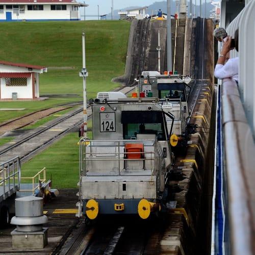 電気機関車によるけん引作業、ぎりぎりの幅を通航するのでスリル満点 | パナマ運河