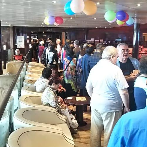 これ、見物客ではありません。ダイニングがオープンするのを待つ長蛇の列がレストランの前から溢れて、隣のラウンジにまで達している状況… | 客船コスタ・ネオロマンチカのダイニング、乗客、船内施設