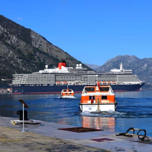 コトル湾に錨泊するクイーン・エリザベス号とテンダーボート。 | コトルでの客船クイーン・エリザベス