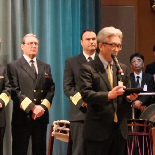 神戸市長より歓迎のメッセージを受ける。左端に立つのは、先頭のAlistair Clark 氏。 | 神戸での客船クイーン・エリザベス