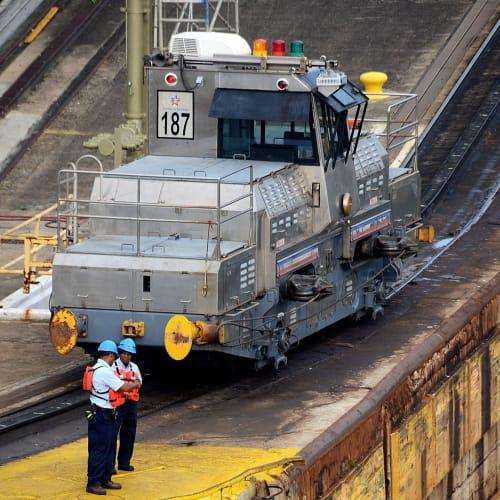 船は閘門通過時エンジンを止める。船は左右から電気機関車でけん引され移動する。この電気機関車は川崎重工、三菱重工の日本製、ぎりぎりの幅をけん引するのでかなりの精度が必要である | パナマ運河