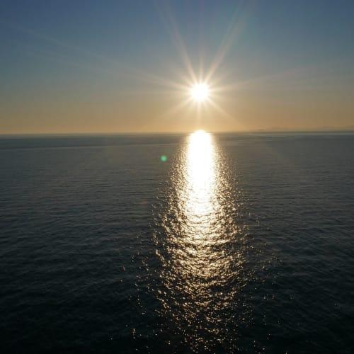 ビールで喉を潤しながらベランダからアドリア海に沈んで行く夕日を眺める | サントリーニ島