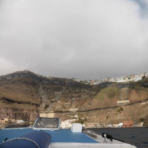 テンダーボートで船着き場へ、崖の上にあるのがフィラの街 | サントリーニ島での客船ルイス・オリンピア