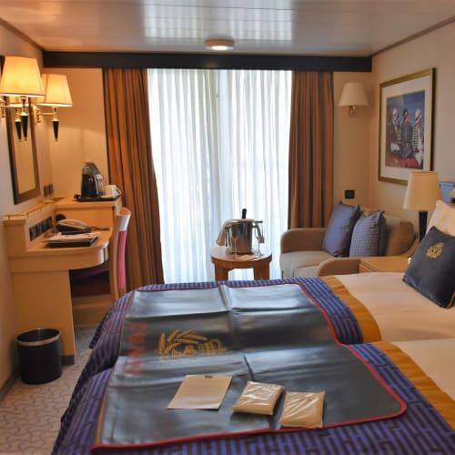 私どもが使った船体後部のバルコニー付き部屋です。  ベットマットの上に置いてある二つのビニール袋には雨ガッパが入っていました。 | 客船クイーン・エリザベスの客室
