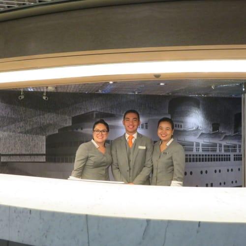 フロントはゲストサービスの一環で24時間対応のスマホやパソコンの受付・相談窓口の役割を果たしており、スタッフはいつも笑顔で接客対応。 | 客船ニュー・アムステルダムのクルー、船内施設