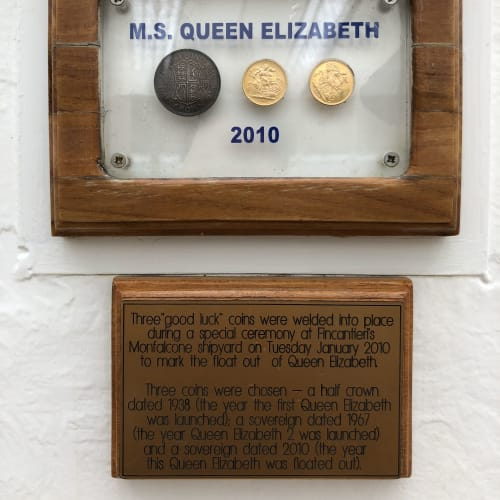 左から初代QE、QE2、現QE就航年のコインが、そーっと飾られています   客船クイーン・エリザベスの船内施設