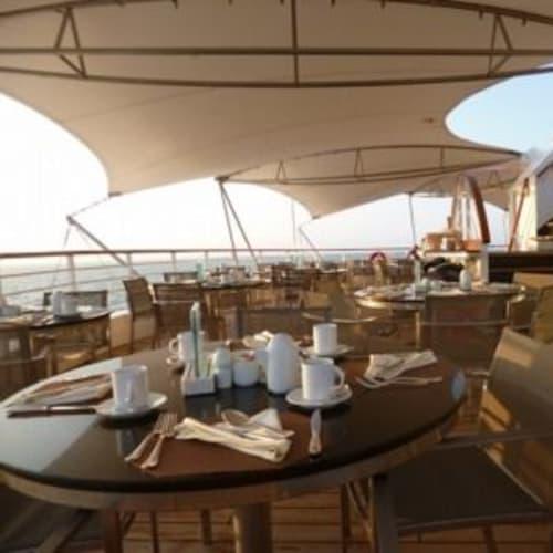 デッキで心地よい風を感じながらの食事がいつも楽しみ。 | 客船シーボーン・レジェンドのダイニング、船内施設