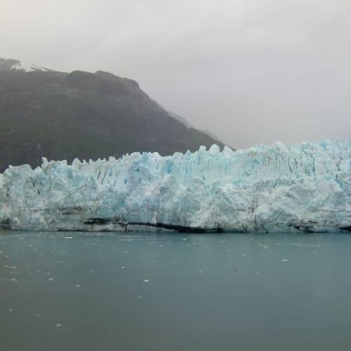グレイシヤーベイ国立公園 Glacier Bay早朝から午後にかけて、クレイシヤーベイ国立公園lを終日クルージング。 1794年英国人探検家ジョージ・バンクーバーによって高さ1200m、幅30kmを超える氷河が発見され、またそのあと米国人ジョン・ミュアが氷河が70km後退していたことを発見した。 かつてインディアンが「偉大なる氷河の湾」と呼んだダイナミックなフィヨルドの景観とともに、アザラシやイルカ、トドなど100 種類以上の動物が生息する、魅力溢れる航路であるが動物は殆ど見れない。 10時頃 最も青色が美しいランプール氷河(Lamplugh),1130頃、氷河の末端のマージョリー氷河(Margerie)をクルーズ、客室のバルコニーで、雨だけど暖房のきいた客室から氷河の素晴らしい景観を見ることができる。   グレイシャーベイ(アラスカ州)