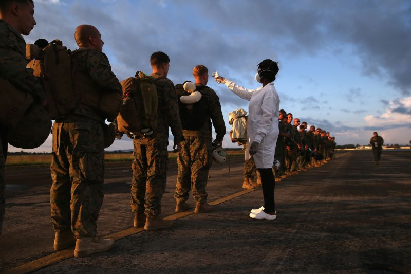 A health worker takes the temperature of U.S. Marines arriving to take part in Operation United Assistance on October 9, 2014 near Monrovia, Liberia.