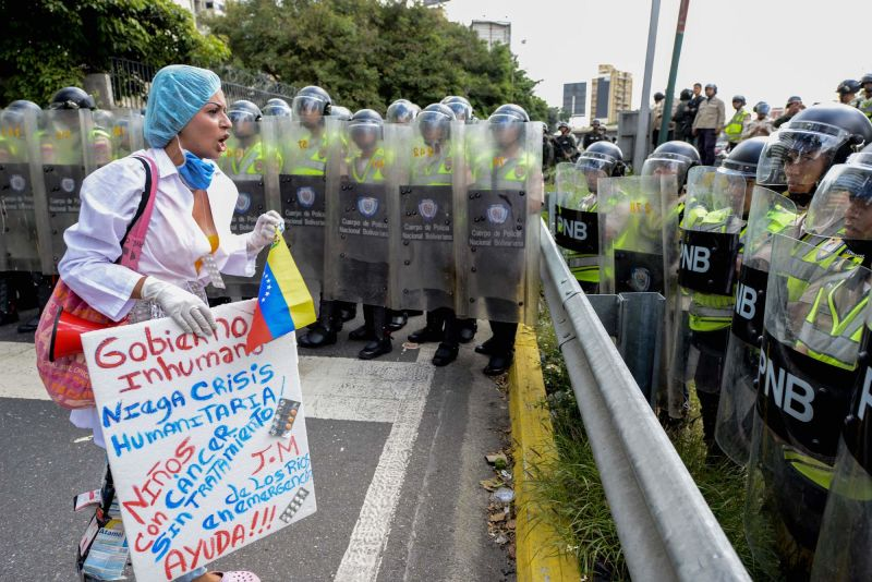 A health care worker carrying a banner confronts police agents during a demonstration against President Nicolas Maduro's government, the lack of medicines and low salaries in the country, in Caracas on February 7, 2017.