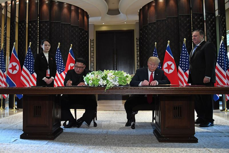 US President Donald Trump (2nd R) and North Korea's leader Kim Jong Un (2nd L) sign documents as US Secretary of State Mike Pompeo (R) and the North Korean leader's sister Kim Yo Jong (L) look on at a signing ceremony during their historic US-North Korea summit, at the Capella Hotel on Sentosa island in Singapore on June 12, 2018. - Donald Trump and Kim Jong Un became on June 12 the first sitting US and North Korean leaders to meet, shake hands and negotiate to end a decades-old nuclear stand-off.