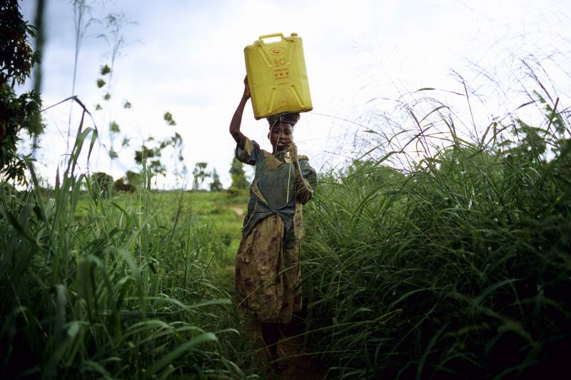 LALIYA, UGANDA - MAY 26: Gladys Aromo, age 12, carries a container with drinking water while walking to her house on May 26, 2005 in Laliya, Uganda. Gladys is a night commuter, one of about 20,000 children that sleep in Gulu town, as they are afraid of being abducted by the Lord's Resistance Army (LRA).