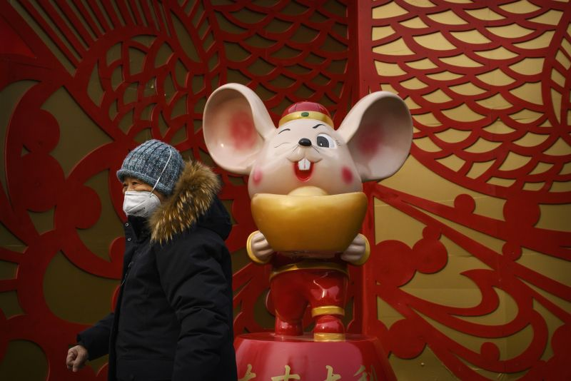 BEIJING, CHINA - JANUARY 26: A Chinese woman wears a protective mask as she walks by a display marking the