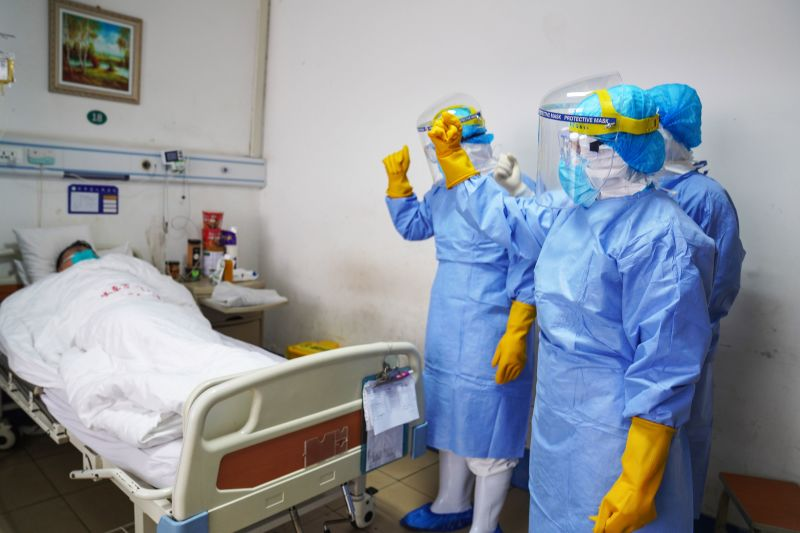 This photo taken on January 28, 2020 shows medical staff members cheering up a patient infected by the novel coronavirus in an isolation ward at a hospital in Zouping in China's easter Shandong province.