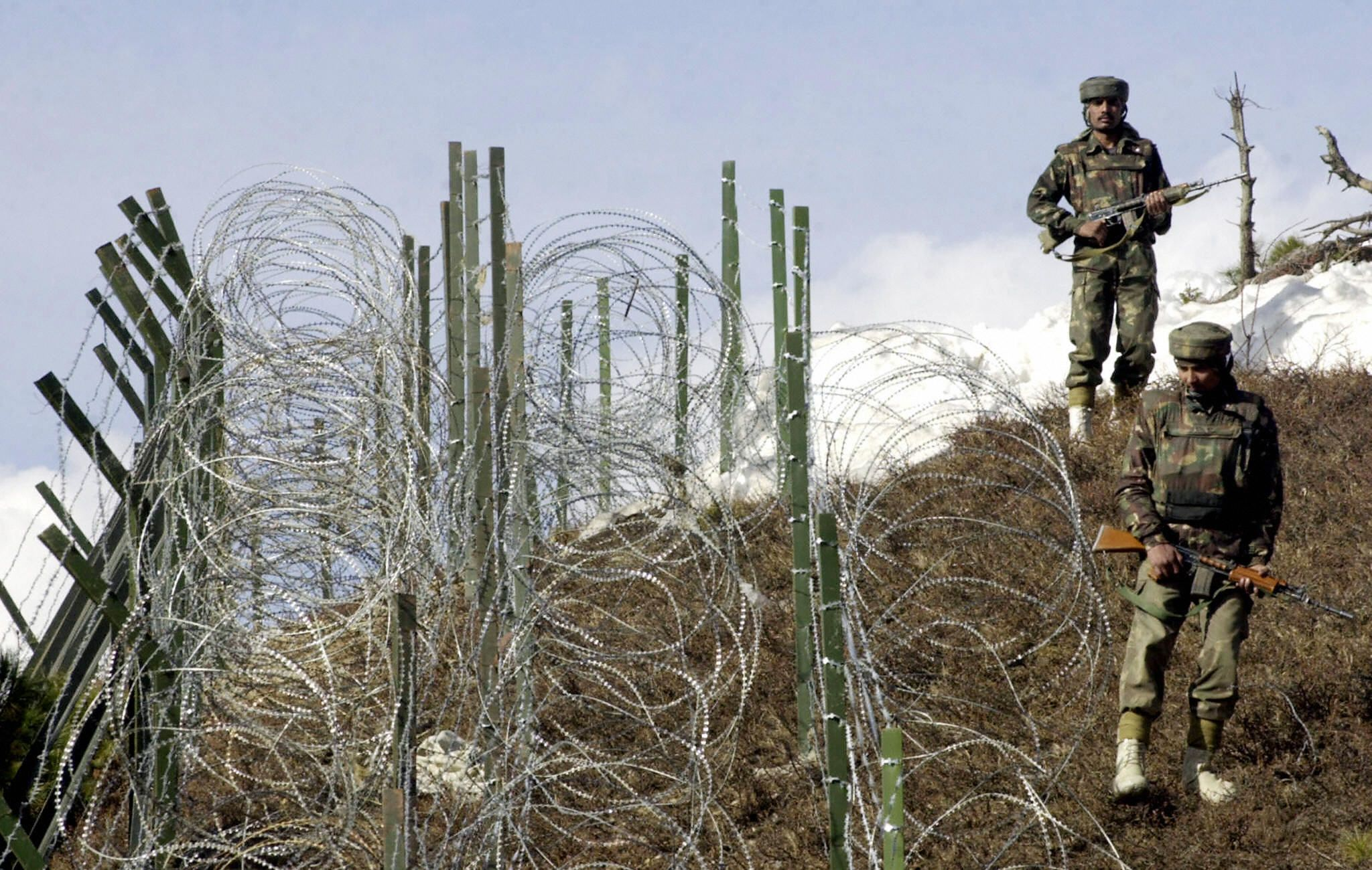 Indian soldiers patrol along a barbed-wire fence, 04 December 2003, near Baras Post on the Line of Control (LoC) between Pakistan and India some 174 kilometers north west of Srinagar. (SAJJAD HUSSAIN/AFP via Getty Images)