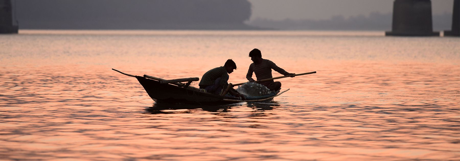 Fishermen paddle their boats back after fishing in the Brahmaputra River on the outskirts of Guwahati. (BIJU BORO/AFP/Getty Images)
