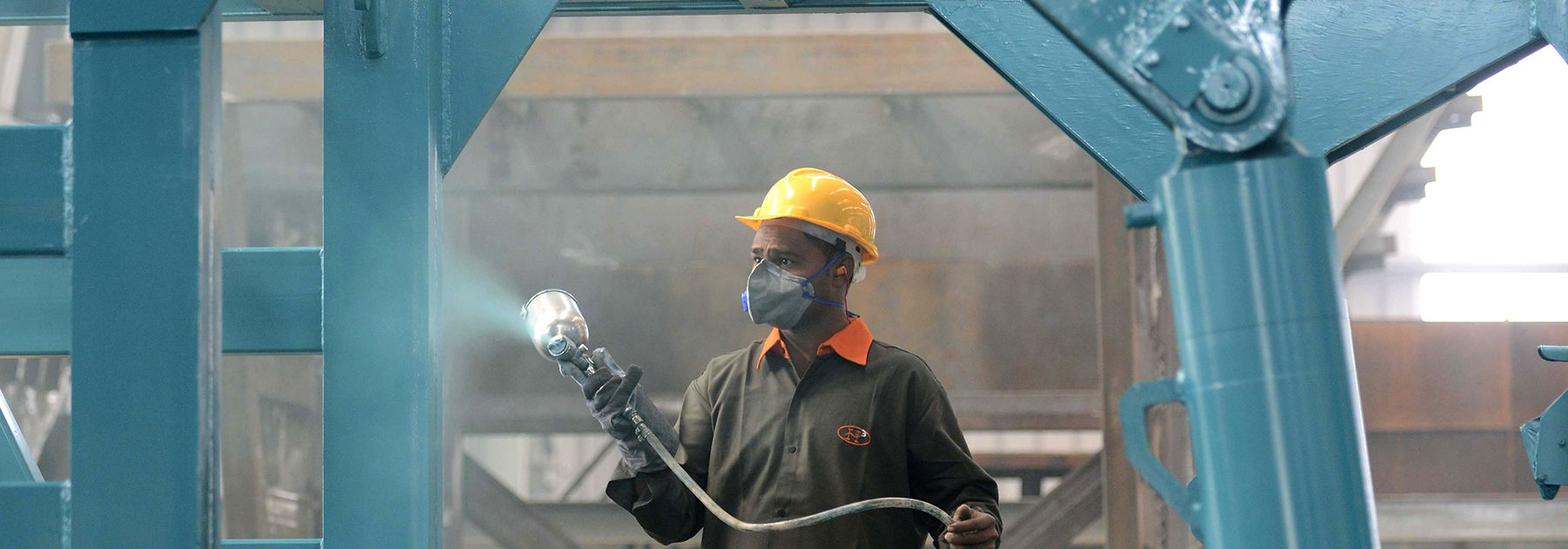 A worker spray paints a steel frame at a heavy fabrication manufacturing factory in Vasna Buzarg village. (SAM PANTHAKY/AFP/Getty Images)