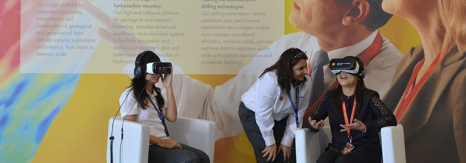 An employee of Shell company (C) helps visitors take a tour of Shell refineries using Virtual Reality goggles in Bangalore. (MANJUNATH KIRAN/AFP/Getty Images)