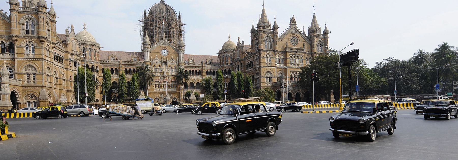 Compressed Natural Gas (CNG) taxis are driven past Chhatrapati Shivaji (Victoria) Terminus train station in Mumbai. (SAJJAD HUSSAIN/AFP/Getty Images)