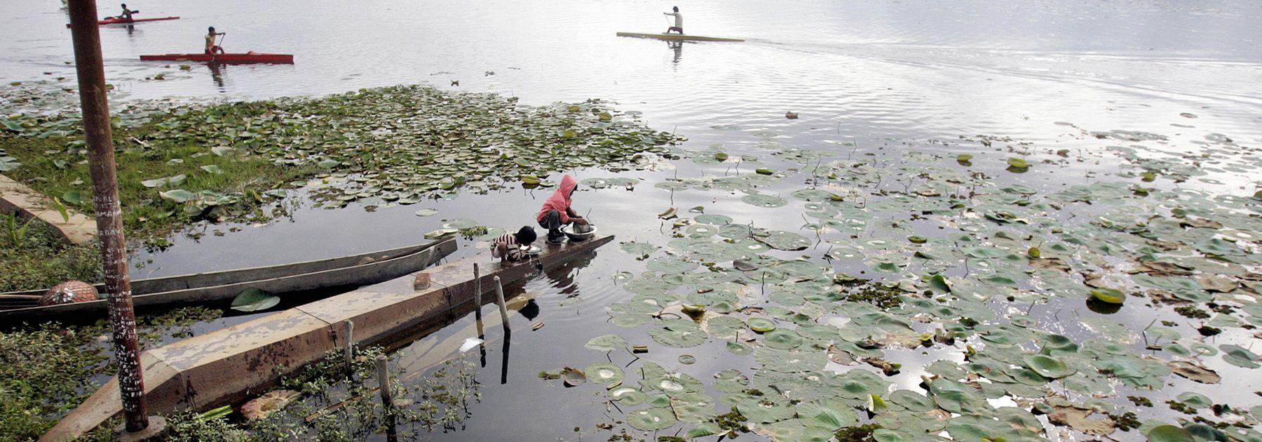 Manipuri children wash utensils as Indian youth paddle kayaks across Loktak lake, the largest freshwater lake in northeastern India. (DESHAKALYAN CHOWDHURY/AFP/Getty Images)
