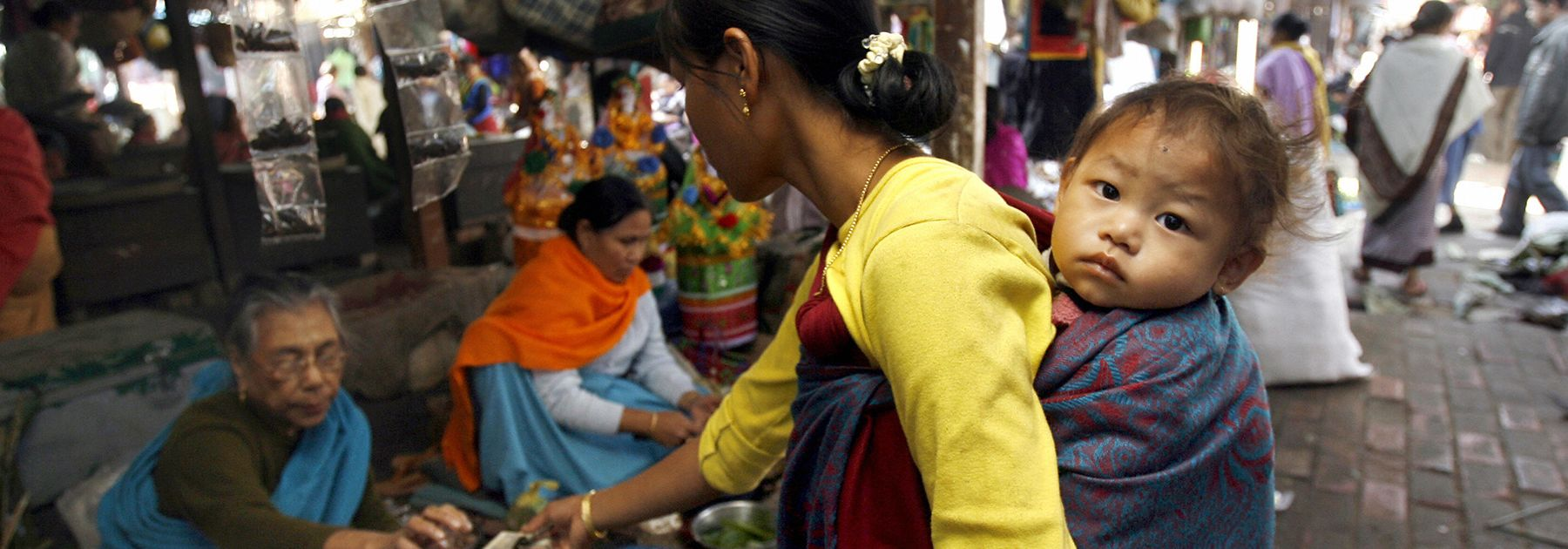 A Manipuri woman, carrying a child on her back, purchases goods from a vendor at the Ima Market (mother's market) in Imphal. (DESHAKALYAN CHOWDHURY/AFP/Getty Images)