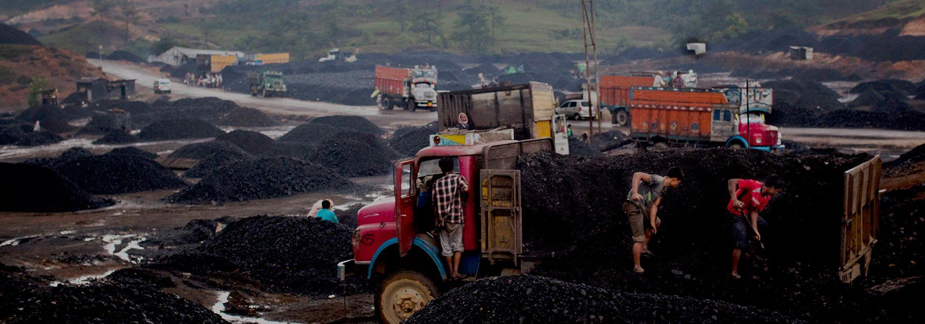 Workers load coal onto trucks at a coal depot near Lad Rymbai. (Daniel Berehulak/Getty Images)