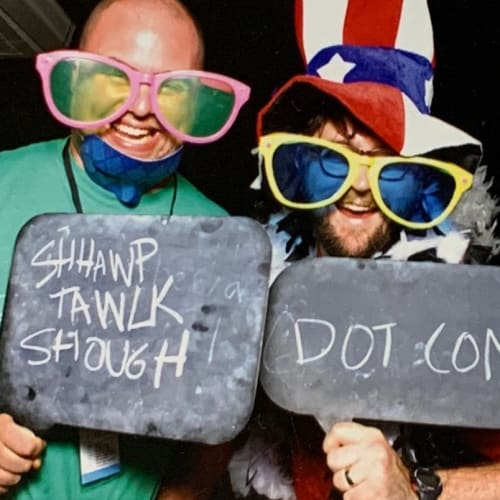 Chris Coyier and Dave Rupert in silly sunglasses and a sign that says Shawp Tawlkk Shough DOT COM