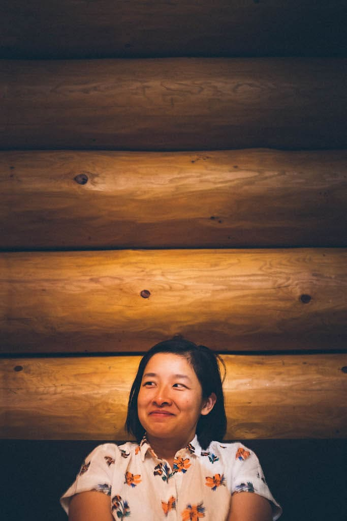 Sarah in front of a wooden wall