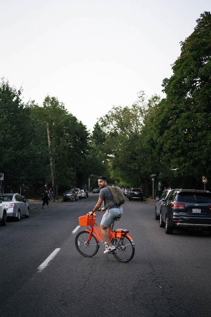 Payam crossing the street on a bike