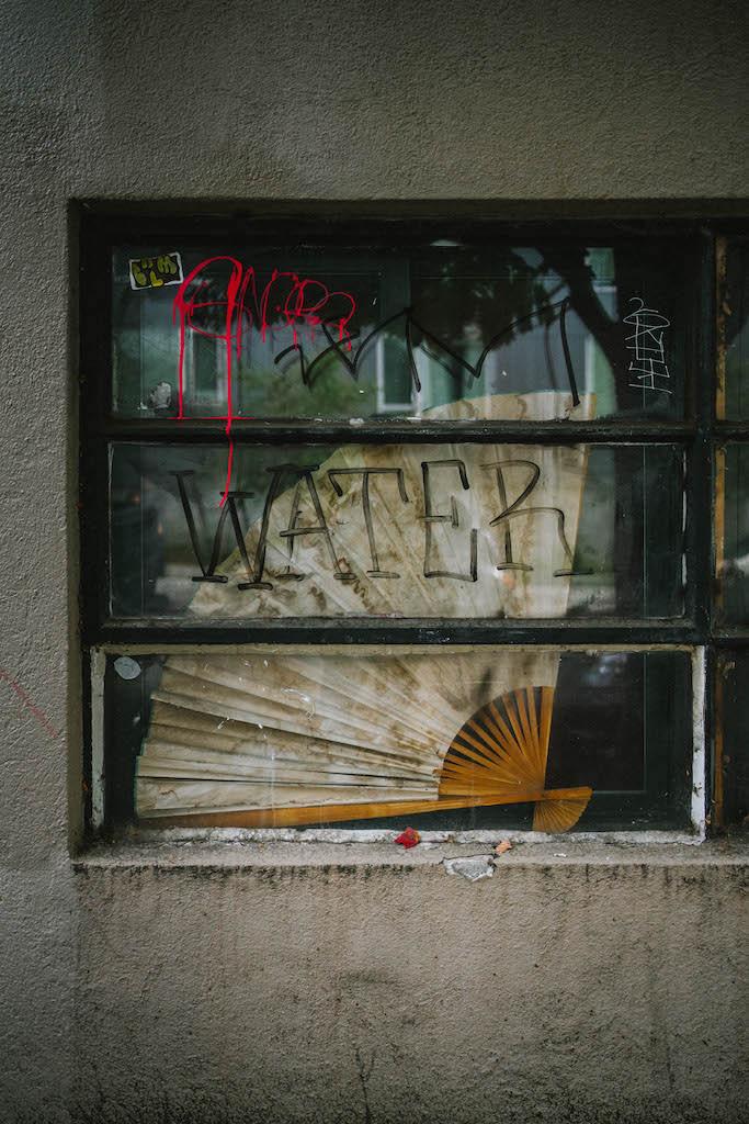 Restaurant window with graffiti saying 'water'