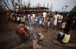 A woman moves a pot of water as people queue for food in a camp for people displaced in the aftermath of Cyclone Idai in Beira, Mozambique, March 26, 2019